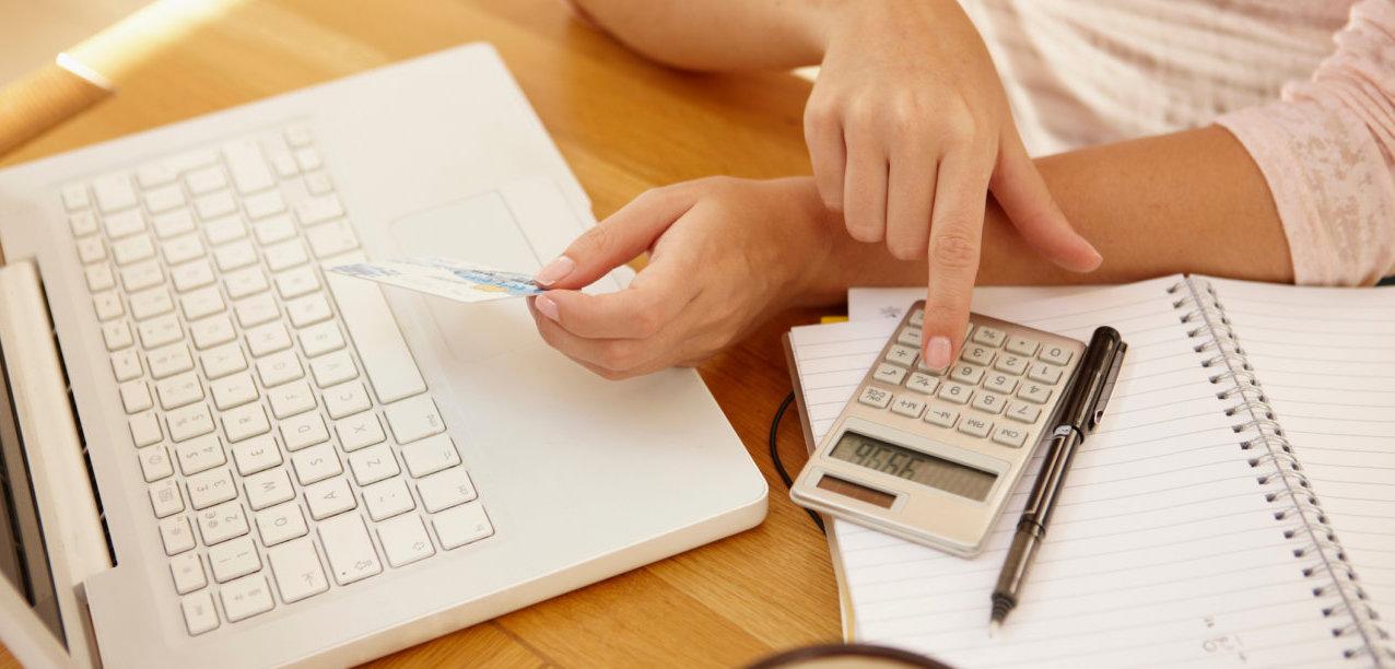 Женские руки, ноутбук и калькулятор